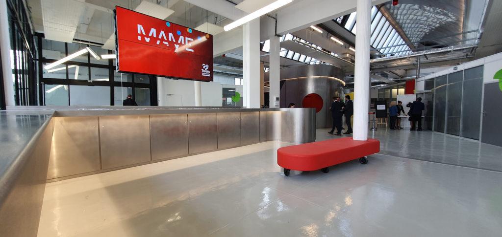 La boutique est conçue pour l'accueil, l'exposition temporaire, la promotion du lieu ou d'évènement et la vente d'objets conçus à MAME. Une assise ludique et mobile, rouge Prouvé, s'enroule autour des piliers de structure de l'entrée pour en gérer le flux.