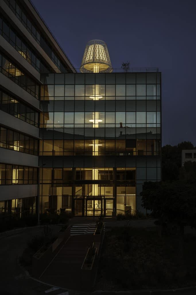 """La lampe traverse la tour de bas en haut, du pied au rez-de-chaussée à l'abat-jour sur le toit terrasse au 5e étage. Si l'immeuble est investi par une seule société, elle fédérera les équipes. Sinon elle créera des """"liens et des interactions"""" entre les plateaux, qui """"contribuent à la force du collectif et de la culture d'entreprise"""", selon Mathieu Sakkas, directeur général de Dragon Rouge."""